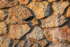 被日光照射了石墙的片段 免版税库存照片