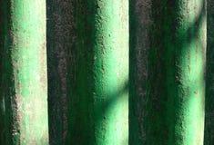 被日光照射了绿色被绘的波浪板岩背景 破旧的多灰尘的波浪板岩纹理 图库摄影