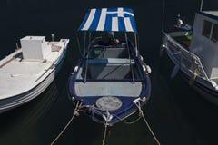 被日光照射了蓝色、绿松石和白色地中海渔船有希腊旗子的在水在优卑亚岛- Nea Artaki,希腊 库存照片