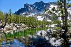被日光照射了高山森林、清楚的湖和花岗岩山 免版税库存图片