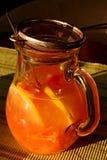 被日光照射了玻璃瓶子用新鲜的橙汁、匙子和不锈的过滤器 库存照片