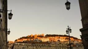 被日光照射了São豪尔赫城堡在从下面Baixa邻里看见的里斯本 免版税图库摄影