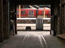 被明确表达的白色公共汽车和红色火车在火车站 免版税图库摄影