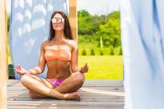 被晒黑和说谎在轻便折叠躺椅由游泳池,暑假的美好的性感的妇女比基尼泳装模型 手段 免版税库存照片