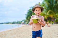 被晒黑的亚裔男孩在帽子和饮料椰子的海滩站立 库存图片