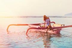 被晒黑的妇女掀动了她的头,当在小船在日落时 在软的焦点 免版税库存照片