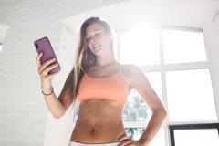 被晒黑的运动的妇女佩带的sportwear和无线耳机在白色晴朗的健身房拿着智能手机手中并且计数卡路里在fi 免版税图库摄影