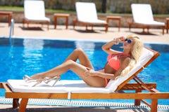 被晒黑和说谎在轻便折叠躺椅的美好的性感的妇女比基尼泳装模型 免版税库存照片