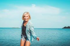 被晒黑的健康中部变老了有获得牛仔布的衣裳的妇女乐趣 激活,在晴朗的夏日享受概念,户外 免版税库存图片