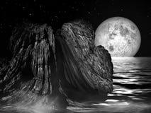 被月光照亮夜-海岩石风景 免版税库存图片