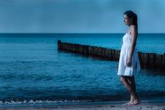 被月光照亮海滨的美丽的冥想的妇女 免版税库存图片