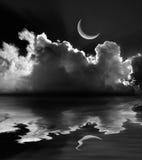 被月光照亮蓬松云彩和新月形月亮反射在黑白 免版税库存照片