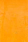 被染黄的橙色灰泥墙壁纹理背景 图库摄影