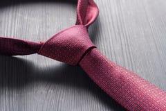 被栓的红色在一张黑暗的桌上的一条领带 免版税库存照片