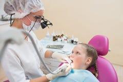 被检查和治疗牙的寸镜双筒望远镜的年轻女性牙医儿童患者坐在牙齿椅子 免版税库存照片