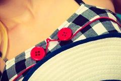 被检查的礼服、红色按钮和太阳帽子 库存图片