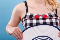 被检查的礼服、红色按钮和太阳帽子 免版税图库摄影