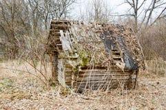 被毁坏射线、日志和棍子一点木被放弃的被破坏的佝偻病打破的村庄房子的老老在原野 库存图片