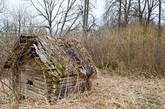 被毁坏射线、日志和棍子一点木被放弃的被破坏的打破的村庄房子的老在原野 图库摄影