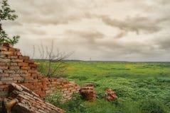 被毁坏的墙壁的片段从农业大厦的在云彩下的领域 免版税库存图片