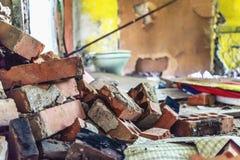 被毁坏的家,堆砖在被破坏的墙壁模糊的背景中  图库摄影