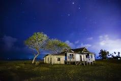 被毁坏的摒弃木房子在晚上有星和多云天空背景 库存图片