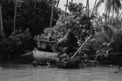 被毁坏的摒弃渔夫小船在河沿a附近搁浅了 免版税库存照片