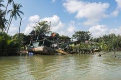 被毁坏的摒弃渔夫小船在河沿a附近搁浅了 免版税库存图片