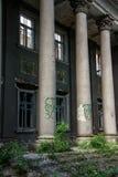 被毁坏的被形成的老行政房子在城市环境里 图库摄影