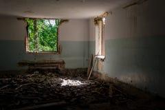 被毁坏的被形成的老行政房子在城市环境里 免版税库存照片