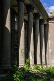 被毁坏的被形成的老行政房子在城市环境里 免版税库存图片