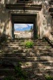 被毁坏的被形成的老行政房子在城市环境里 库存照片