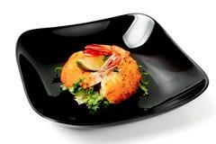 被油炸的虾用在黑色的盘子的莴苣 免版税库存照片