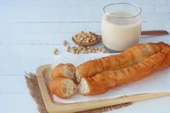 被油炸的面团黏附与一杯热的大豆豆牛奶 免版税图库摄影