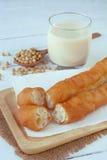 被油炸的面团黏附与一杯热的大豆豆牛奶 图库摄影
