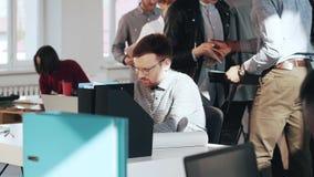 被注重的和疲乏的年轻英俊的欧洲男性业务经理与膝上型计算机一起使用在繁忙的现代办公室桌上 股票录像