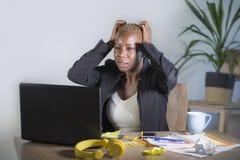 被注重的和被挫败的美国黑人的黑人妇女工作被淹没和被弄翻在办公室便携式计算机书桌打手势哀伤和d 免版税图库摄影