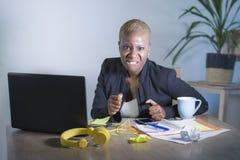 被注重的和被挫败的美国黑人的黑人妇女工作被淹没和被弄翻在办公室便携式计算机书桌打手势恼怒  免版税库存照片