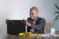 被注重的和被挫败的美国黑人的黑人妇女工作被淹没和被弄翻在办公室便携式计算机书桌打手势恼怒  免版税库存图片