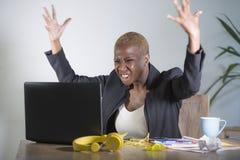 被注重的和被挫败的美国黑人的黑人妇女工作被淹没和被弄翻在办公室便携式计算机书桌打手势恼怒  免版税图库摄影