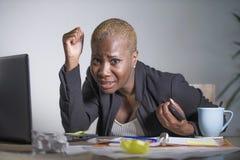 被注重的和被挫败的美国黑人的黑人妇女工作被淹没和被弄翻在办公室便携式计算机书桌打手势绝望 免版税库存图片