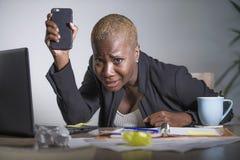 被注重的和被挫败的美国黑人的黑人妇女工作被淹没和被弄翻在办公室拿着手机的便携式计算机  免版税图库摄影