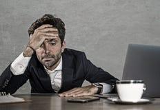 被注重的商人感觉压下了并且淹没了工作在疲倦的办公计算机书桌并且用尽了击败由事务f 免版税库存照片