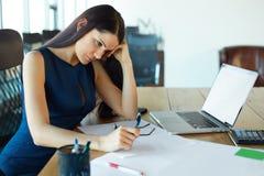 被注重的女商人在她的工作地点 企业例证JPG人向量 免版税图库摄影