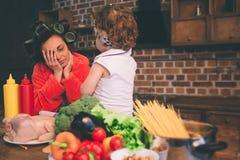 被注重的妈咪在家 有小孩的年轻母亲在家庭厨房里 做许多任务的妇女,当照看她时 免版税库存图片
