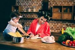 被注重的妈咪在家 有小孩的年轻母亲在家庭厨房里 做许多任务的妇女,当照看她时 图库摄影