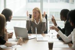 被注重的恼怒的女实业家争论在会议上与男性collea 免版税库存照片