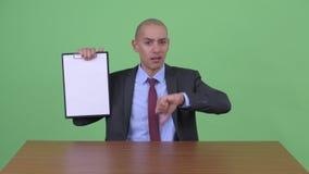 被注重的秃头多种族商人陈列剪贴板和给拇指下来在书桌后 股票录像