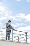 被注重的年轻商人摩擦在大阳台注视反对天空 免版税图库摄影