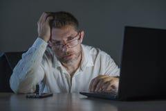 被浪费的和疲乏企业家人工作夜间在办公室手提电脑书桌被用尽和困在财政事务 库存图片